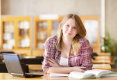 Female student with laptop working in library. looking at camera — Stock Photo