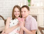 Sonriente joven y su novia linda tienen corazón — Foto de Stock