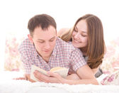 Young cheerful couple reading a book while lying on bed — Stok fotoğraf