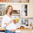 Pregnant woman in kitchen eating a salad smiling — Stock Photo #23570519