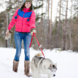 Girl with her cute dog in the winter forest — Stock Photo