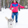 Young happy woman running with her dog — Stock Photo