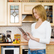 Stock Photo: Pregnant woman using a tablet computer in kitchen.