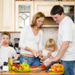 Happy family makes a dinner in kitchen — Stock Photo