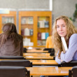 Female student reads the book in library - Foto Stock