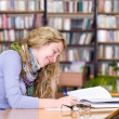 Stock Photo: Female student reads the book in library