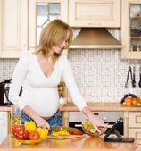 Gravid kvinna med en tablet-dator att laga mat i sitt kök — Stockfoto