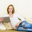 Foto Stock: Pregnant womlying down on sofand using electronic tablet