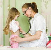 Doctor examining girl with stethoscope — Stock Photo