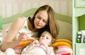 Niño enfermo con fiebre alta, tendido en la cama y madre tomando témpera — Foto de Stock