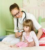 Sick little girl in bed. Doctor with thermometer is sitting near — Stock Photo
