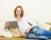 Pregnant woman lying down on sofa and using electronic tablet — Stock Photo