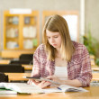 Stock Photo: Female student with electronic pad in library