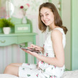Royalty-Free Stock Photo: Smiling young woman with tablet on her bed