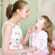 Young mother examining little girl's throat — Stock Photo #24675135