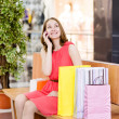 Stock Photo: Shopping womwith bags talking on phone. looking up