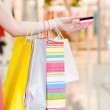 Female hand holding shopping bags and credit card — Stock Photo #24675389