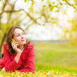 Young woman talking on cell phone in the autumn park — Stock Photo #24675393
