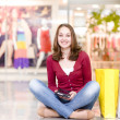 Stock Photo: Smiling girl with shopping bags in shop.