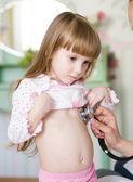 Läkare med hjälp av stetoskop lyssnar på barnets hjärta slå — Stockfoto