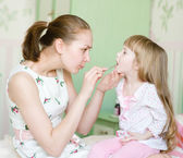 Mother examining little girl's throat — Стоковое фото