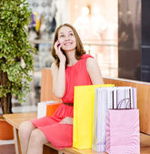 Shopping woman with bags talking on the phone. looking up — Stock Photo