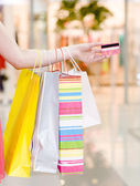 Female hand holding shopping bags and credit card — Stock Photo