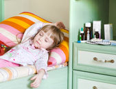 Sick girl lying on a bed — Stock Photo