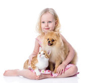 Girl playing with pets - dog and cat. looking away. — Stock Photo