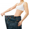 Woman shows her weight loss by wearing an old jeans — Stock Photo