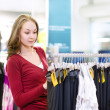 Young woman doing shopping and choosing clothes — Stock Photo