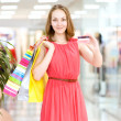 Beautiful young woman with shopping bags and credit card — Stock Photo