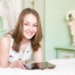 Stock Photo: Smiling young womwith tablet computer on her bed