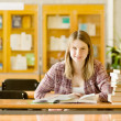 Happy girl with books at the library. looking at camera — Stock Photo