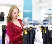 Giovane donna facendo shopping e scegliendo i vestiti — Foto Stock
