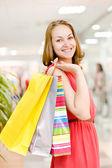 Mooie jonge vrouw met boodschappentassen in winkelcentrum — Stockfoto