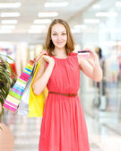 Beautiful young woman with shopping bags and credit card — 图库照片