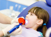 Little girl with open mouth receiving dental filling drying procedure — Stock Photo