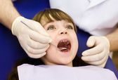 Close-up of little girl opening his mouth wide during inspection — Stock Photo