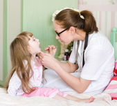 Pediatrician examining little girl's throat — Stock Photo