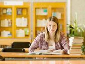 图书馆借书的快乐女孩。看看相机 — 图库照片