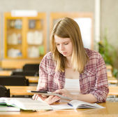 Female student with electronic pad in library — Stockfoto