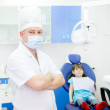 Stock Photo: Portrait dentist with patient in the background. looking at camera
