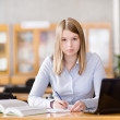 Thoughtful student in library. looking at camera — Stock Photo
