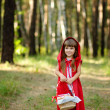 "Girl in the wood with a basket looking at camera. the fairy tale ""Red Riding Hood"" — Stock Photo"