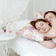 Embracing young couple sleeping on the bed — Stock Photo #25205349