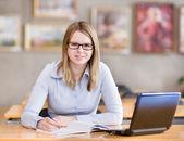 Studentin mit laptop in der bibliothek arbeiten. blick in die kamera — Stockfoto