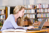 Female student with laptop working in library — Stockfoto