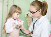 Doctor examining girl with stethoscope — ストック写真