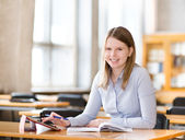 Student with tablet computer in library. looking at camera — Stock Photo